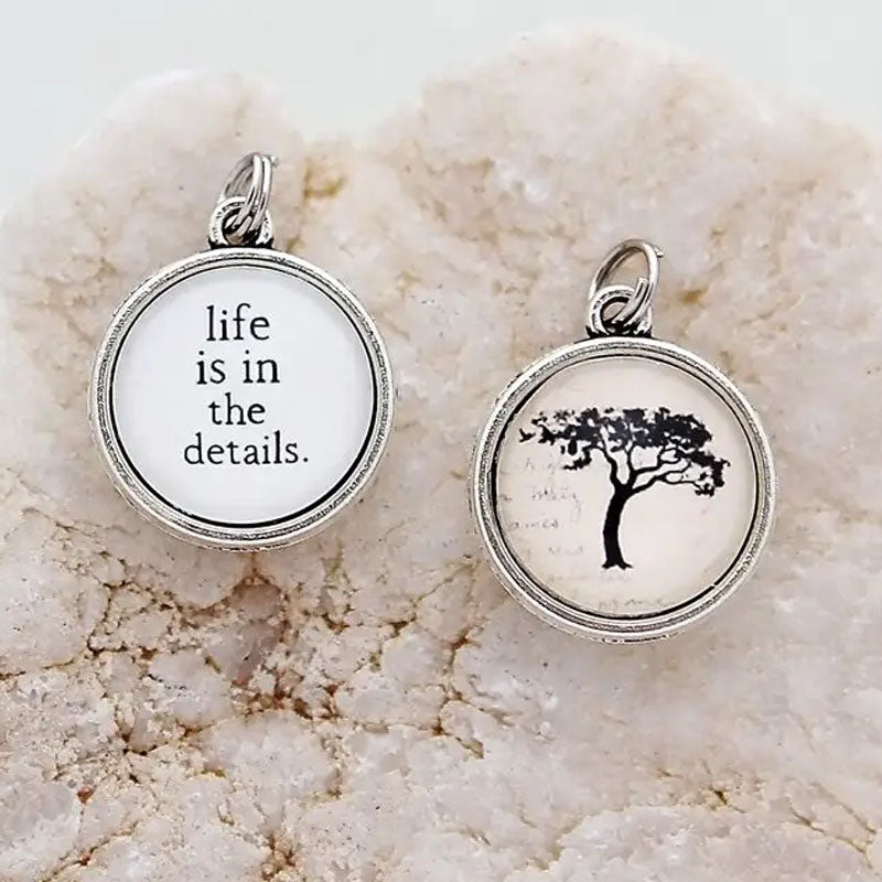 "Necklace pendant that has a tree on one side and the text ""life is in the details."" on the reverse"
