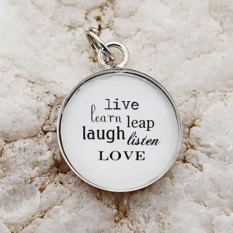 "Round necklace pendant with the words ""live, learn, leap, laugh, listen, love"" printed on a white background."