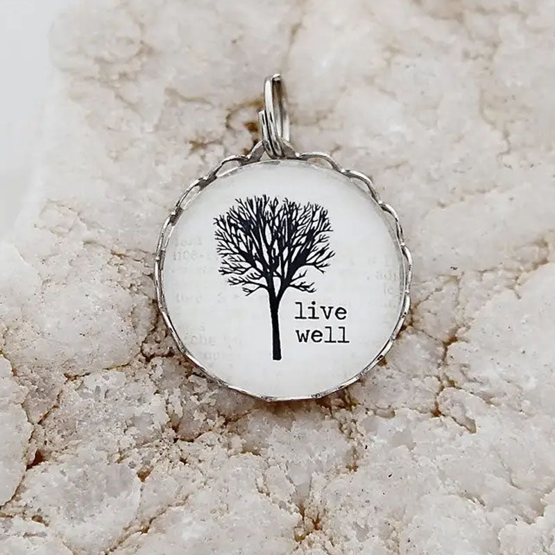"Round necklace pendant with a white background, silver metal edge, and image of a tree with the words ""live well"""