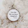 "Round necklace pendant with a white background and silver metal edge that reads, ""Live the life you have imagined. -Thoreau"""