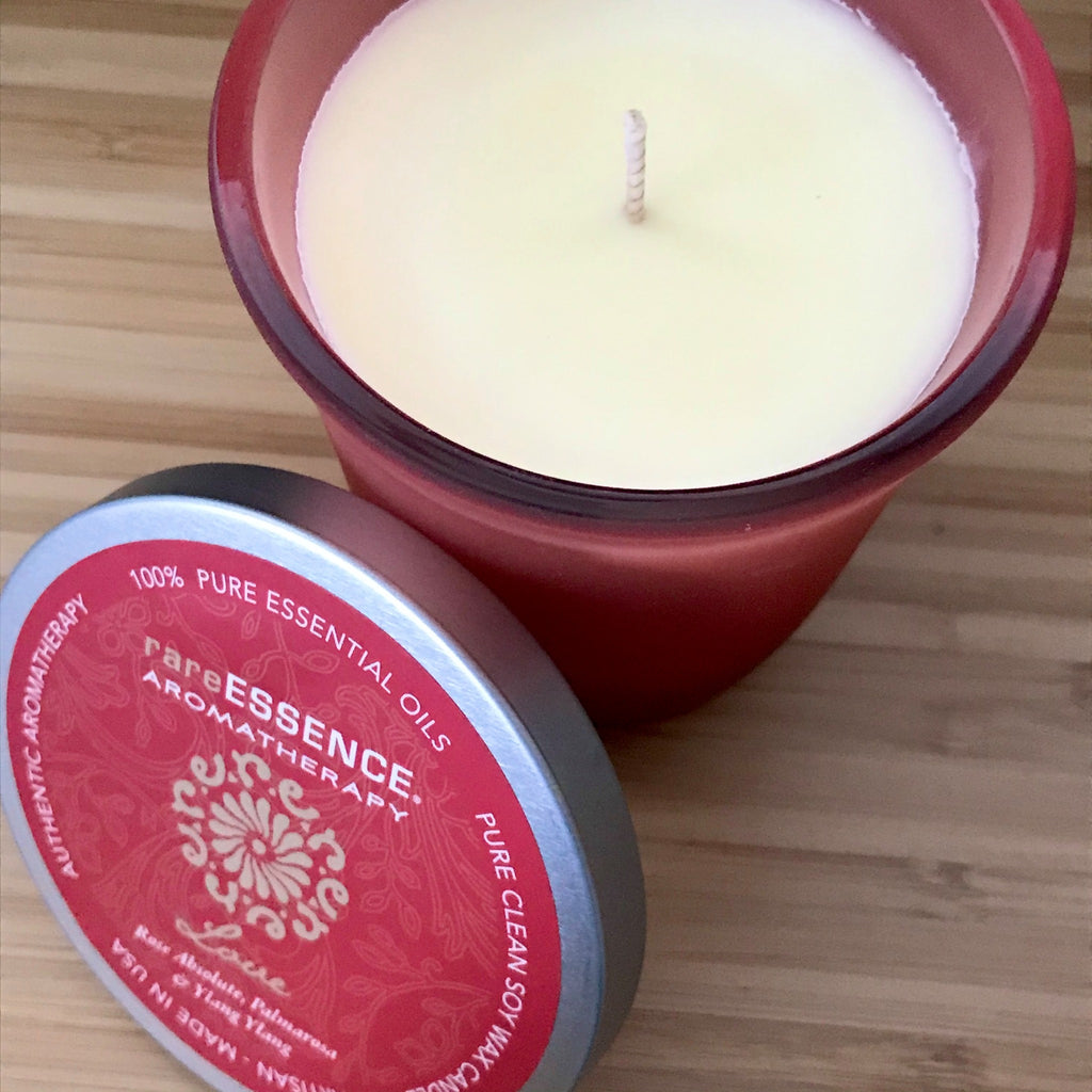 Love soy candle in red frosted glass jar.