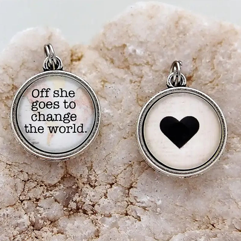 "Reversible necklace pendant with a heart on one side and a map with the text ""Off she goes to change the world."" on the other side."