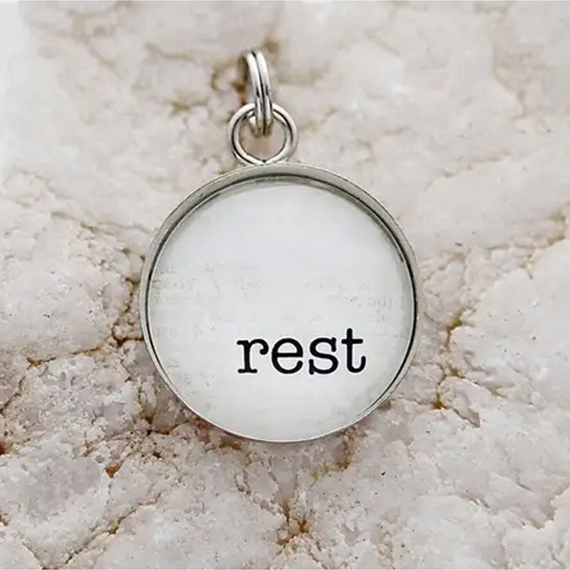 "Round necklace pendant with white background and silver metal edge. Pendant reads ""Rest""."