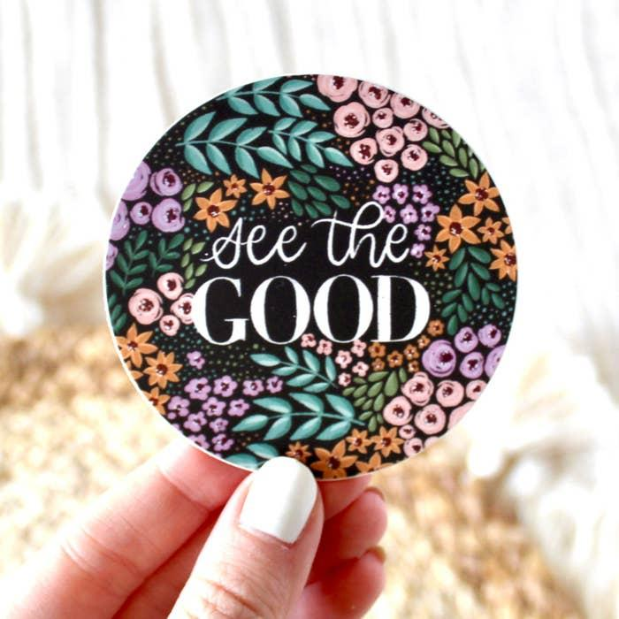 "Sticker with ""see the good"" written in white on a black background and pink, orange, and purple flowers with green leaves."