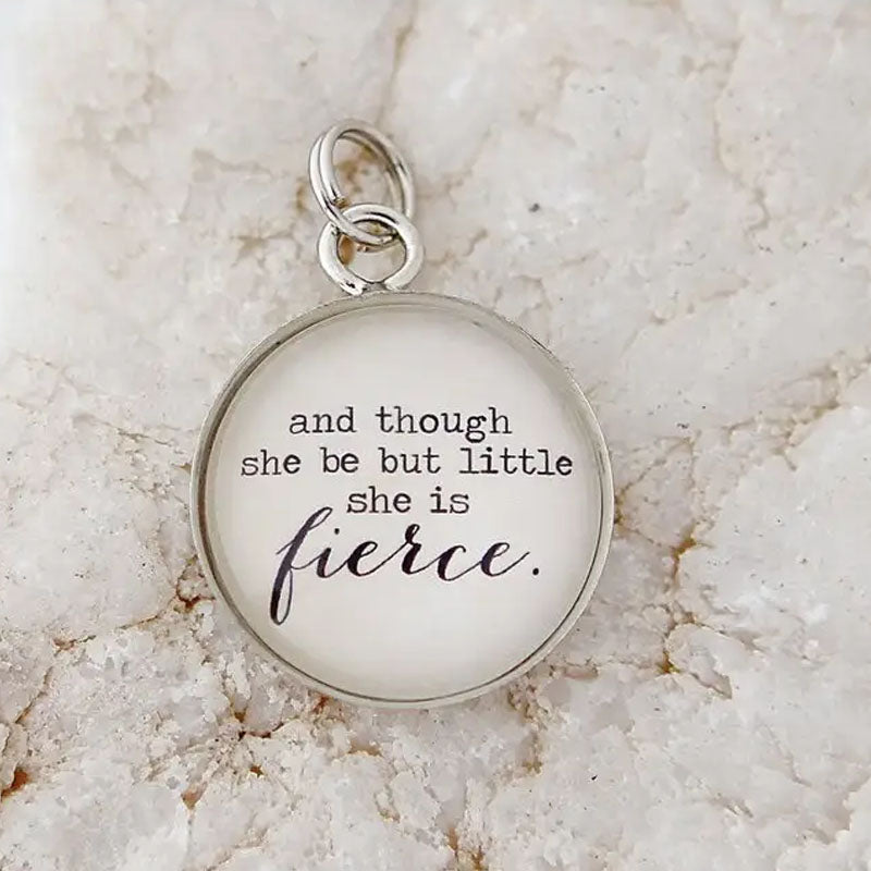 "Round white necklace pendant with silver metal edge that reads ""and though she be but little she is fierce."""