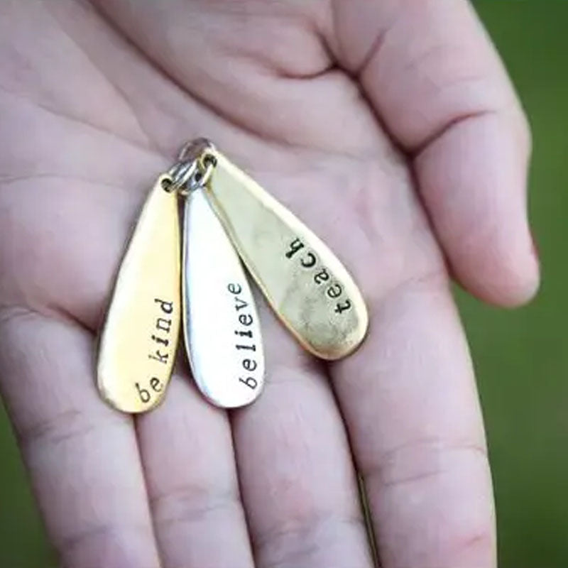 Hand holding 3 teardrop pendants to show scale
