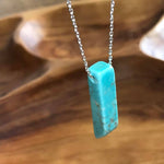 A beautiful turquoise stone pendant shaped into a point at one end hanging from a sterling silver dipped chain.