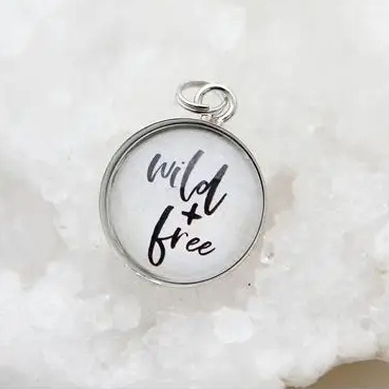 "Round white necklace pendant that reads ""wild and free""."