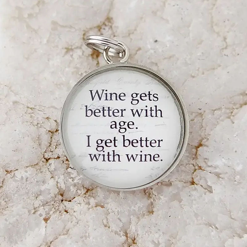 "Round white necklace pendant that reads ""Wine gets better with age. I get better with wine."""