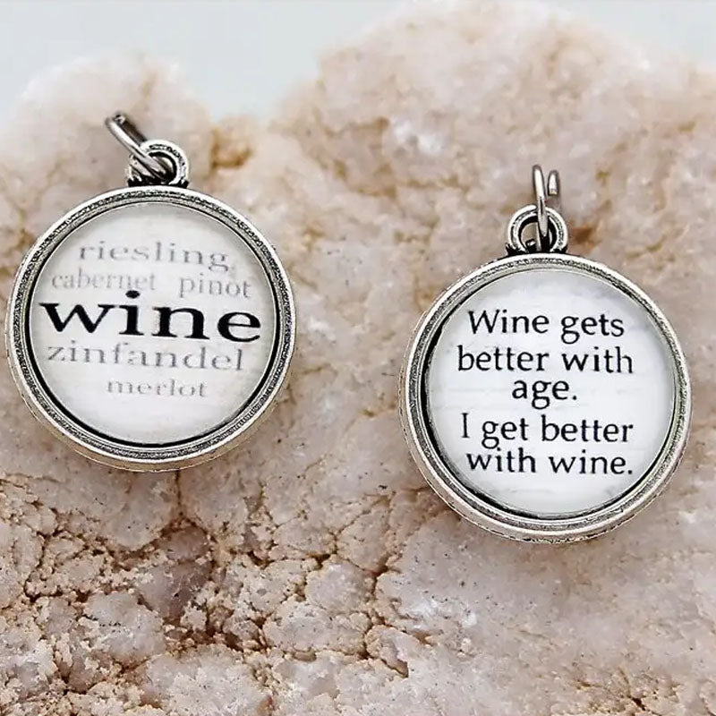 "Reversible necklace pendant that has the word ""wine"" with a list of different wines on one side and on the reverse says ""Wine gets better with age. I get better with wine."""