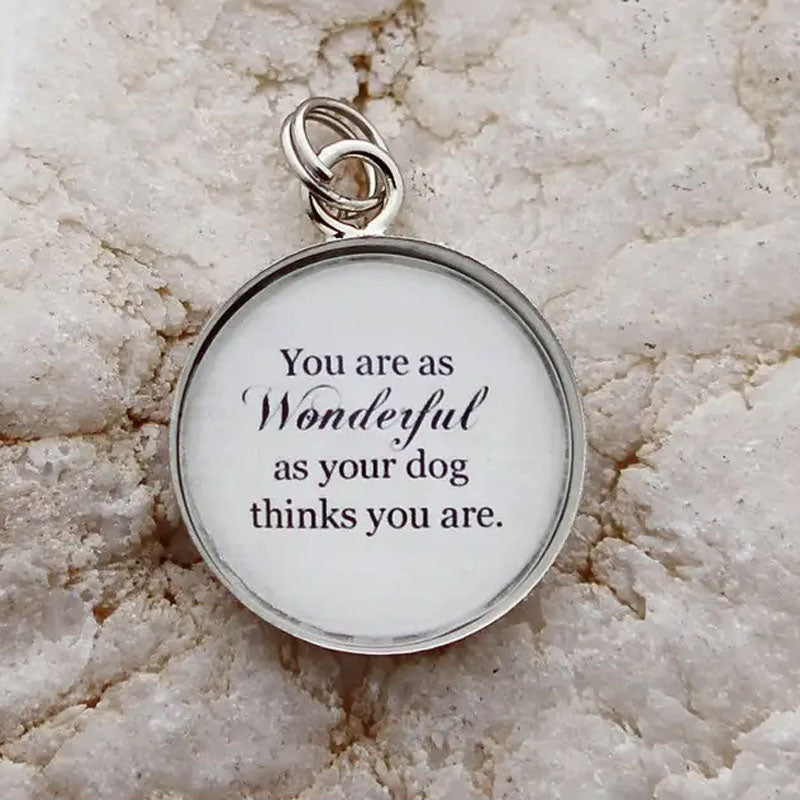 "Round white pendant that reads, ""You are as Wonderful as your dog thinks you are."" The edge of the pendant is silver."