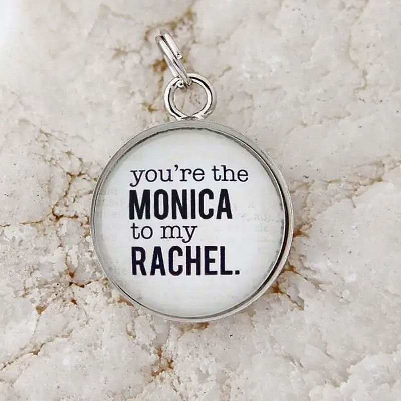 "Round white pendant that reads, ""you're the MONICA to my RACHEL."" The edge of the pendant is silver."