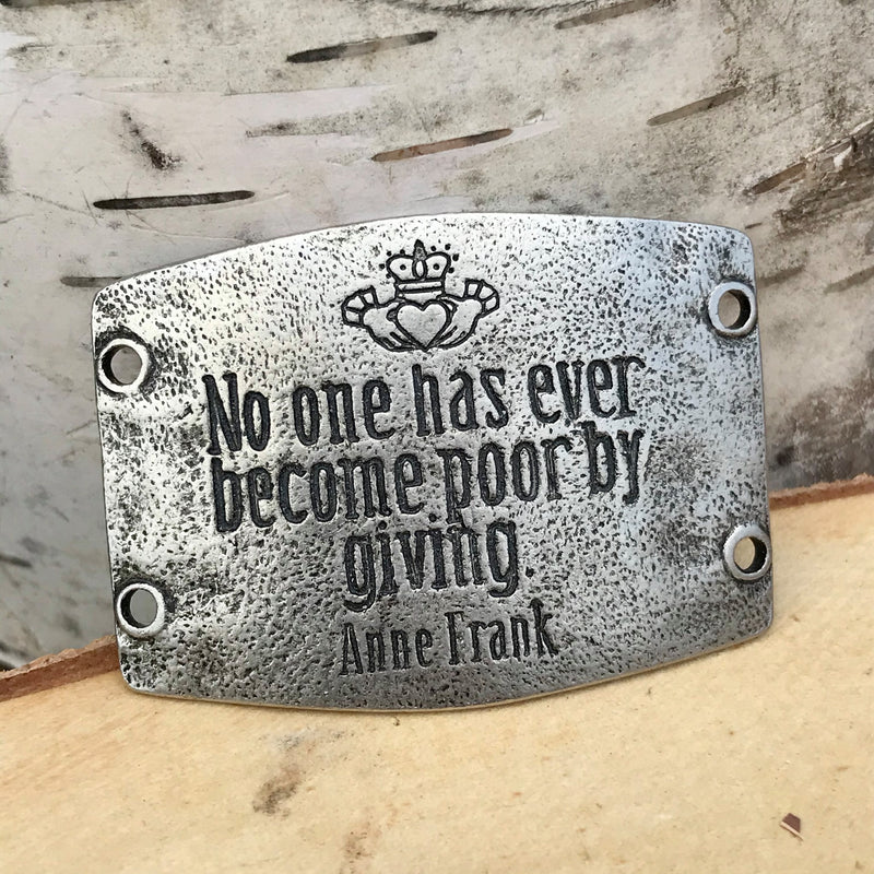 "Antique silver finish Lenny & Eva bracelet sentiment that reads, ""No one has ever become poor by giving."" Quote by Anne Frank. Design above quote is hands holding a heart and crown."