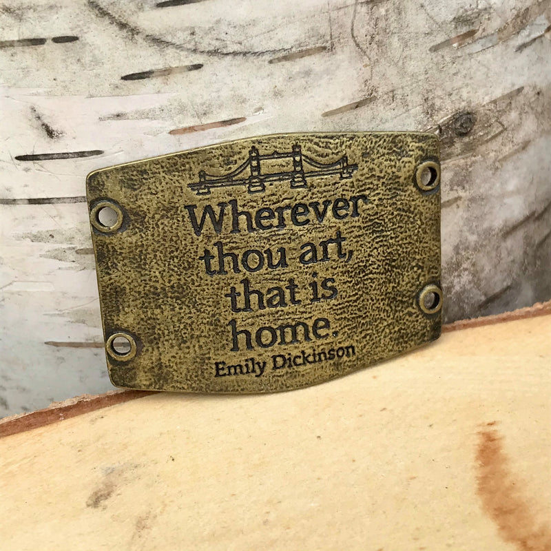 "Antique brass colored Lenny & Eva bracelet sentiment that reads, ""Wherever thou art, that is home."" Quote by Emily Dickinson. Adorned with a bridge design above the quote."