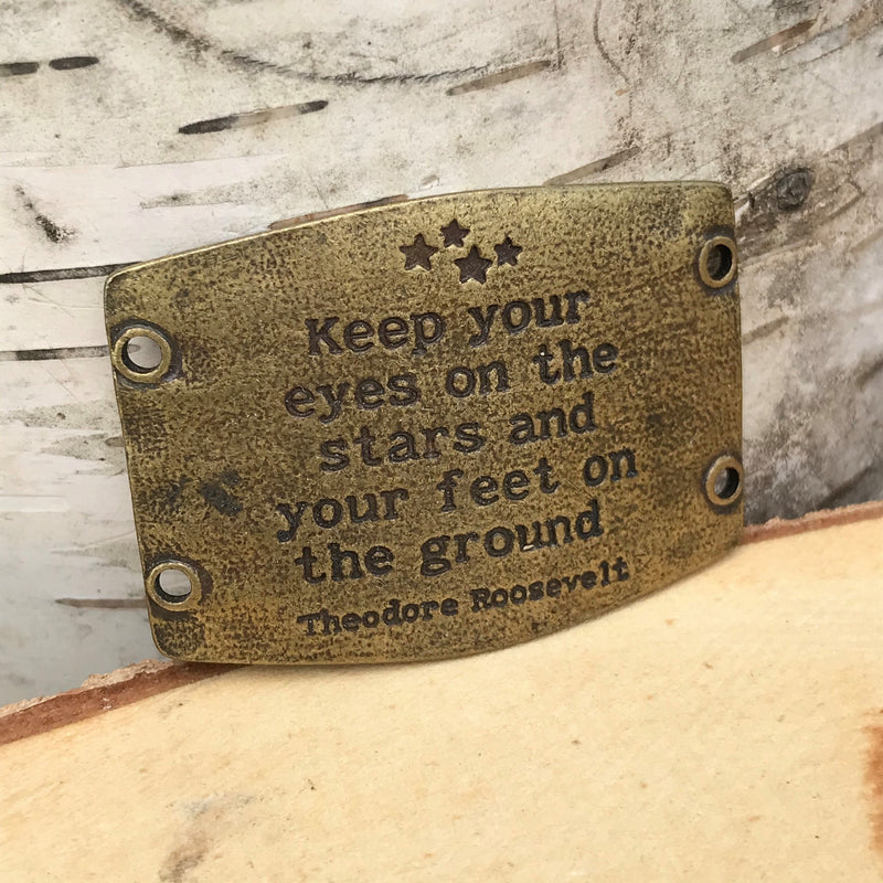 "Antique brass finish Lenny & Eva bracelet sentiment that reads, ""Keep your eyes on the stars and your feet on the ground."" Quote by Theodore Roosevelt. Design of stars above the quote."