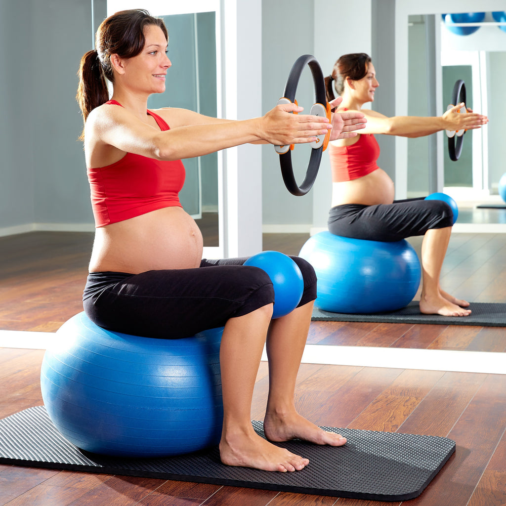pregnant woman using the Pilates Ring Magic Fitness Circle and the exercise ball chair