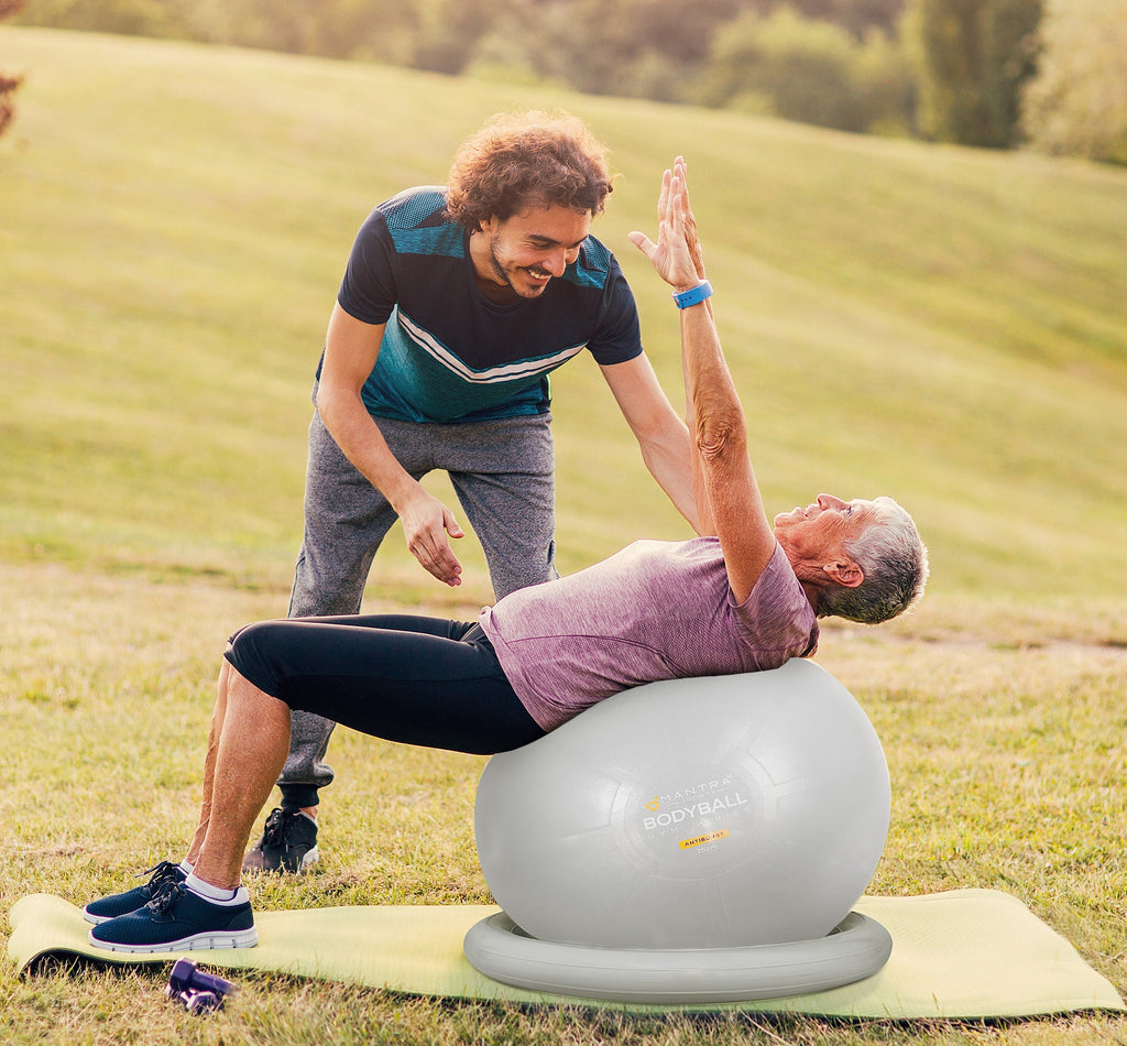 a gym trainer using the exercise ball on his student