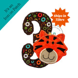 Tiger, birthday number three iron on in bright orange, matching trim on top of large number three in circle print on brown background