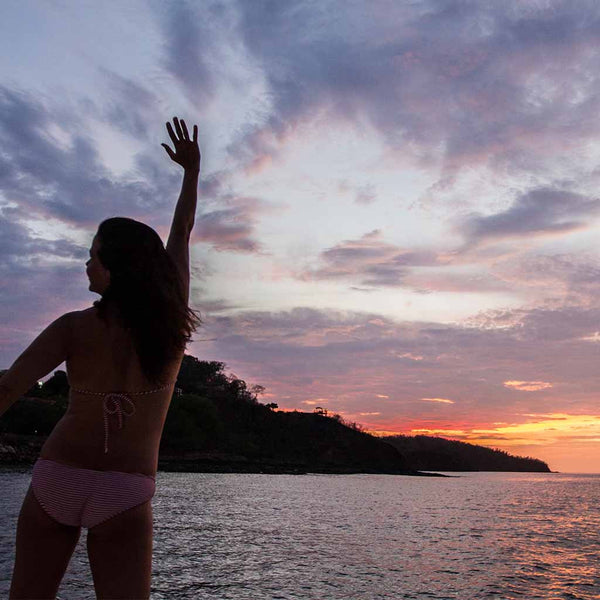 Woman saluting the sunset on boat in costa rica