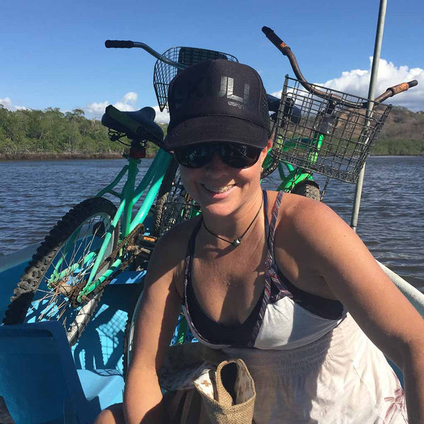 Woman on boat with bike crossing estuary in Costa Rica