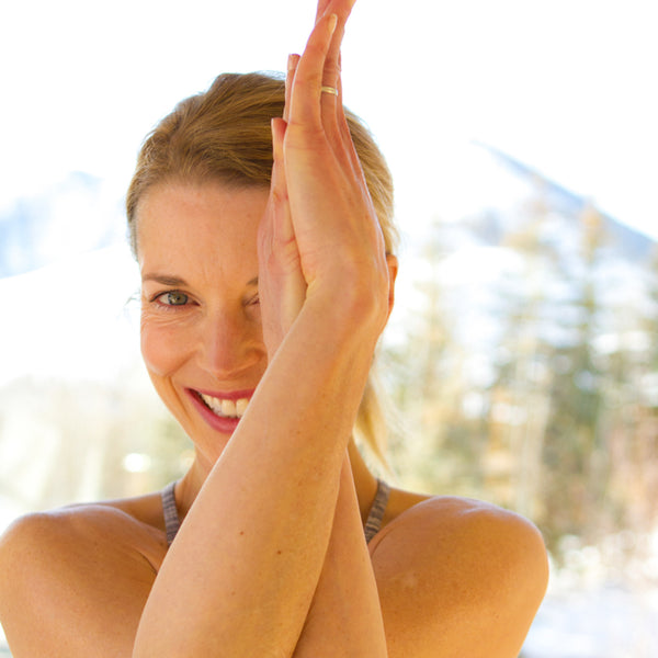 Smiling girl in yoga pose at yoga retreat