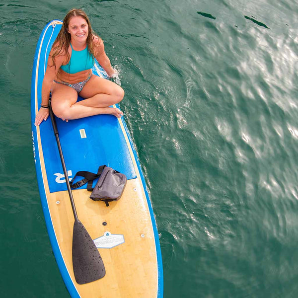 Woman doing yoga on a stand up paddle board