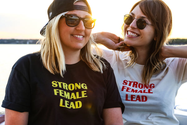 "Strong <br> Female <br> Lead <br> <img src=""https://cdn.shopify.com/s/files/1/1435/9366/t/3/assets/realm-lips.png?1053709037421936823"" alt=""lips""><br> Black and Yellow Shirt"