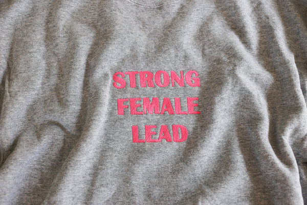 "Strong <br> Female <br> Lead <br> Gray <br> <img src=""https://cdn.shopify.com/s/files/1/1435/9366/t/3/assets/realm-lips.png?1053709037421936823"" alt=""lips""><br> Sweatshirt"