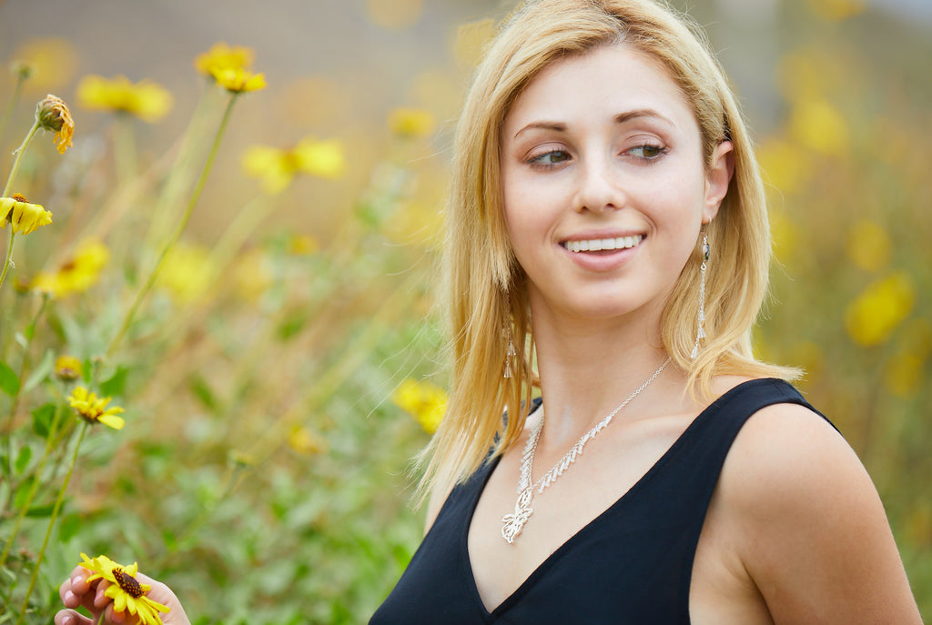 jewelry model wearing short sterling silver pendant necklace and sterling silver chandelier earrings in a field of daisies