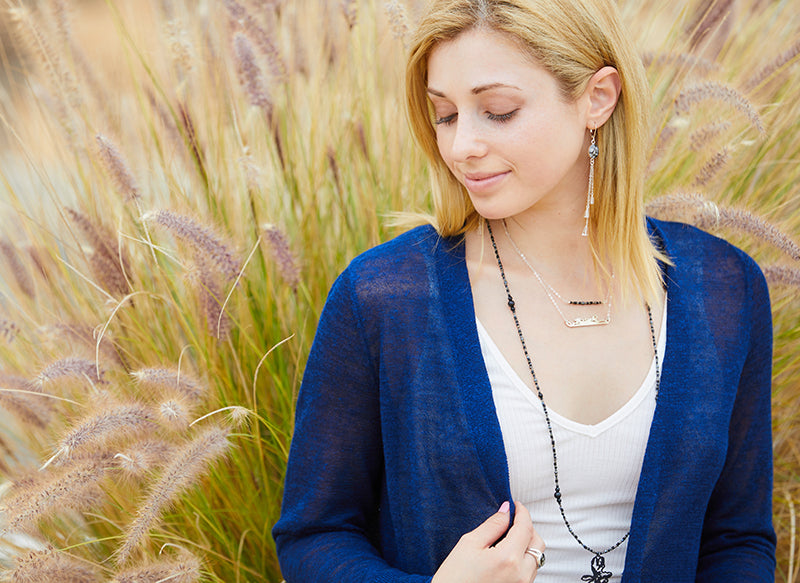 jewelry model wearing beaded necklace and sterling chain in front of cat tail bush