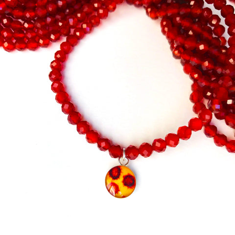 close up of covid 19 image pendant and red carnelian bead stretch bracelet