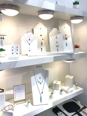 close up of revive jewelry booth product shelves with displayed necklaces, bracelets, rings and earrings