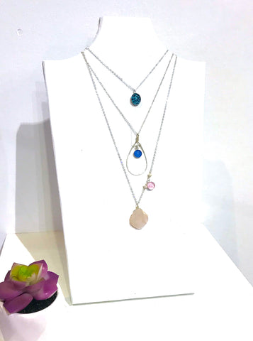 Revive Jewelry necklaces on white neck form and little succulent plant