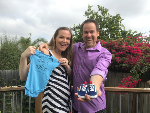 Nikki & husband Rob holding up baby boy Z's onesie and vans to announce his arrival on 3/28/21