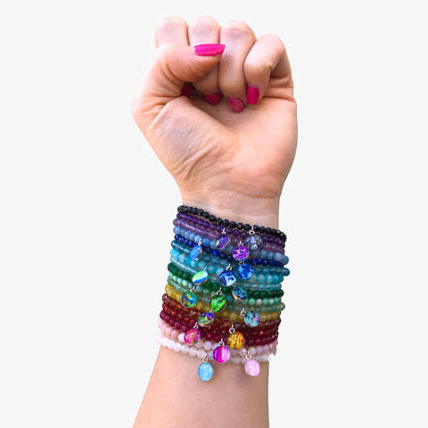 arm stacked with all the illness and disease awareness bracelets in a rainbow of colors