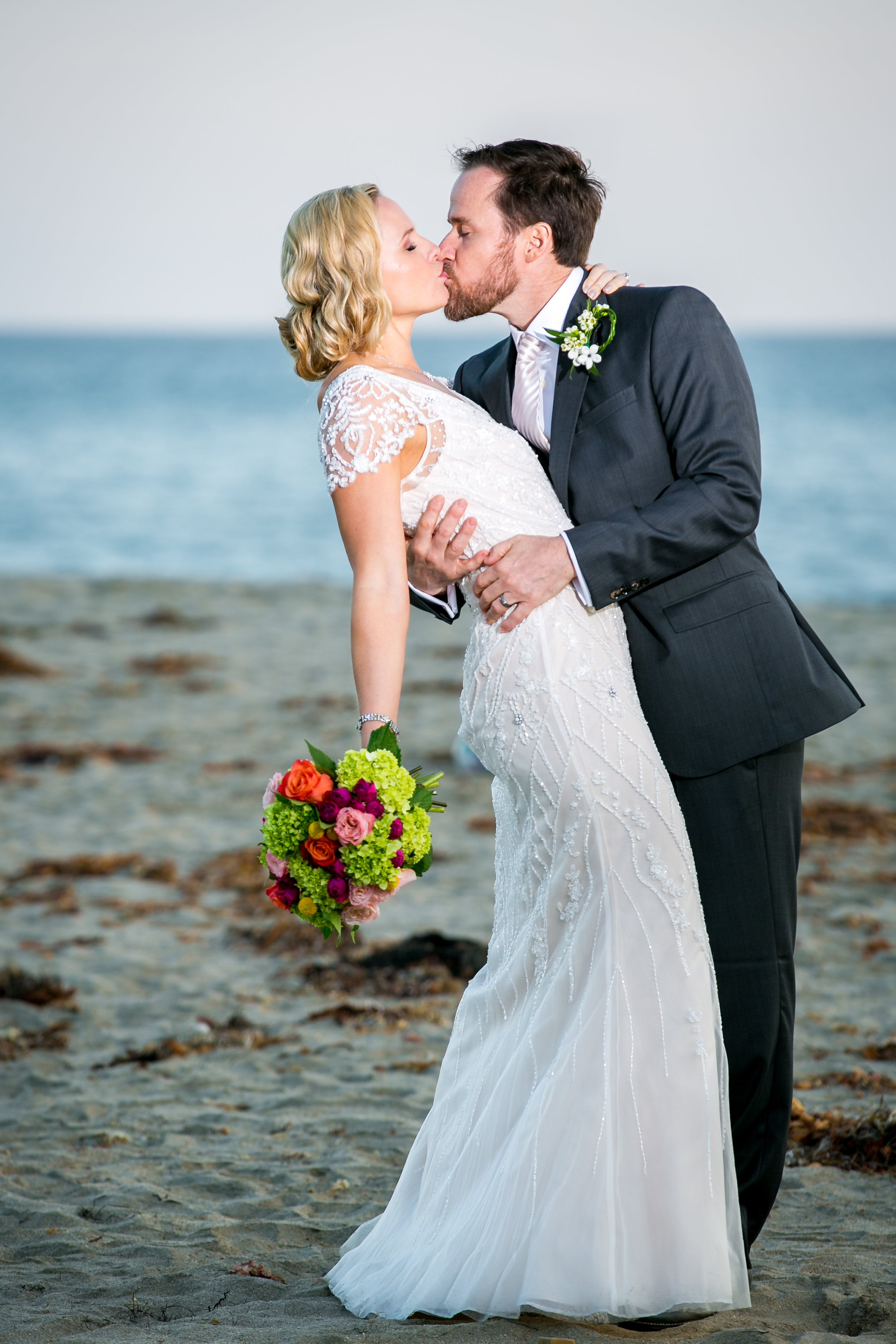 Nikki and Robby kissing on the beach on their wedding day