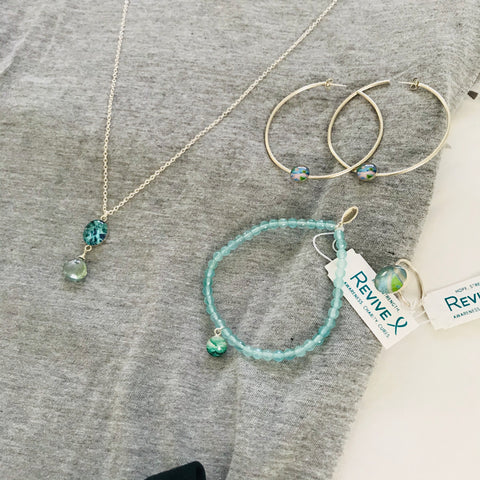 close up of colorful teal and blue jewelry for ovarian cancer, Alzheimer's and infertility awareness gives back to charity