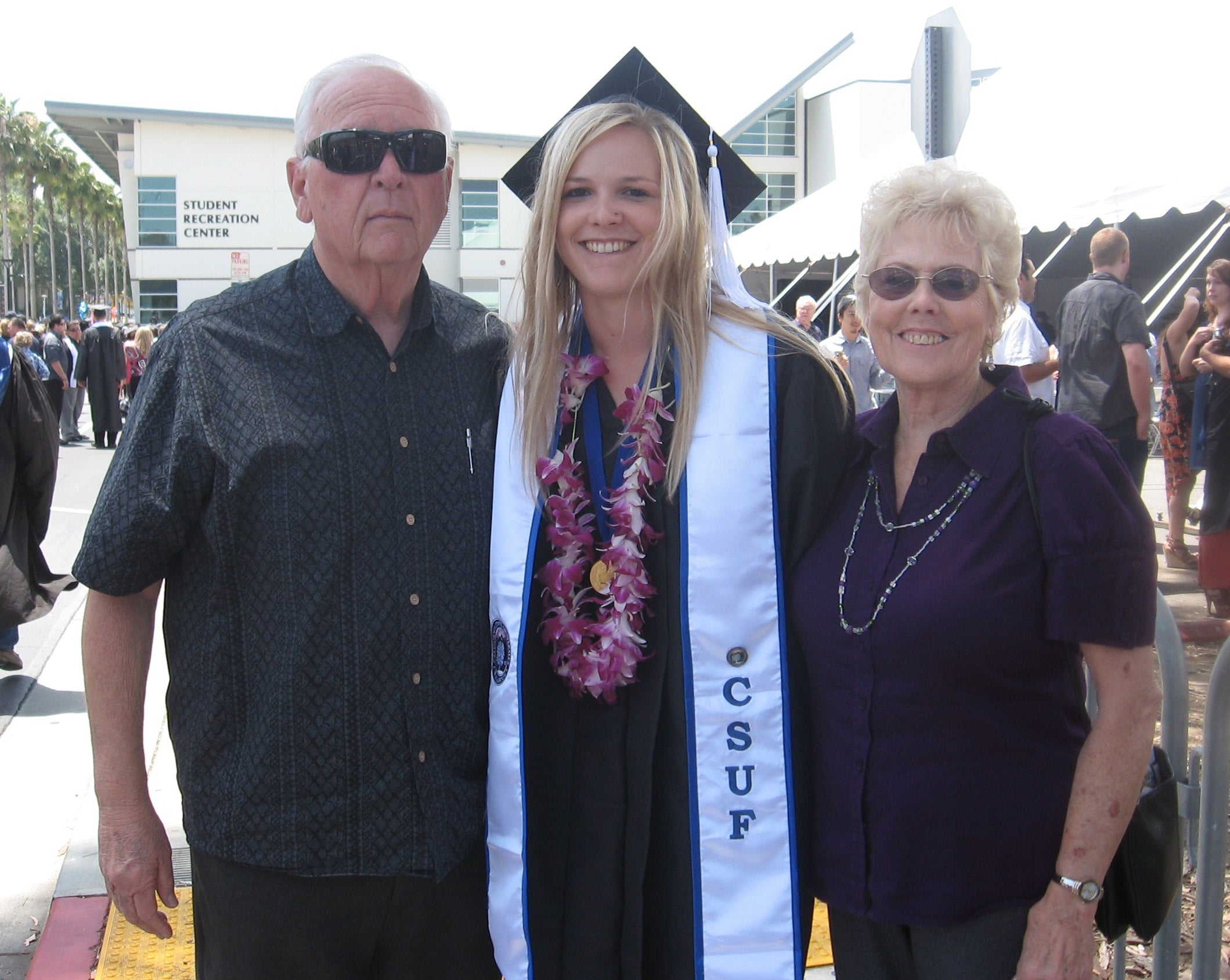 nikki on graduation day from CSUF with her grandma and grandpa