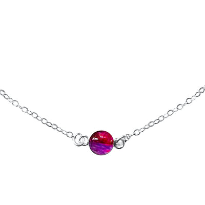 Close up of Circle of hope necklace with 6mm round red and purple pendant with heart disease cell image in resin on sterling silver chain necklace gives back