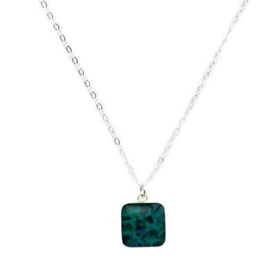 Close up of short sterling silver thin chain necklace with blue and green breast cancer cell image with resin in square pendant
