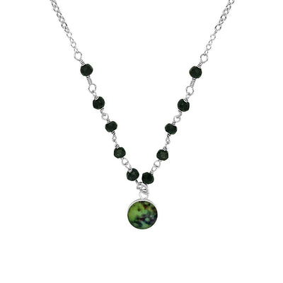 Close up of green, blue and black melanoma cell image under resin in small round pendant hanging from linked black spinel stones across the front and sterling silver chain
