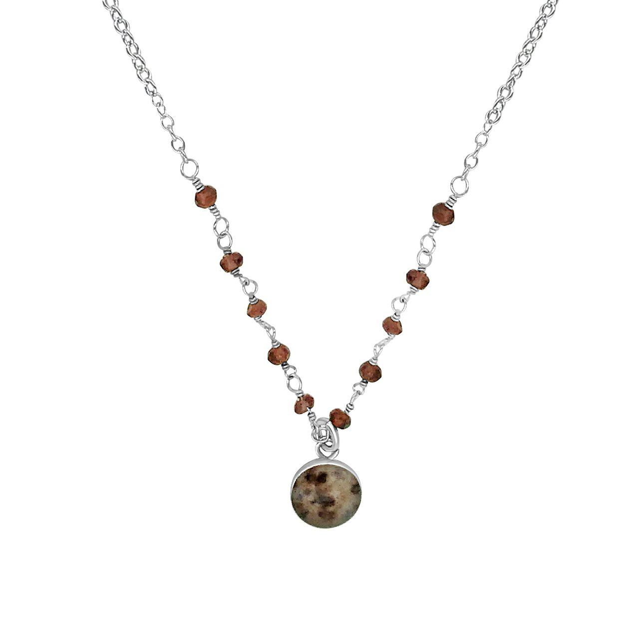 Close up of front and center necklace pendant round brown, beige and maroon pendant of a multiple sclerosis cell image in resin hanging from the center of faceted garnet stones across the front and sterling silver chain