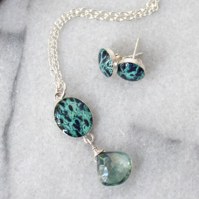 Close up of Ovarian cancer awareness necklace in silver with oval pendant based on cell image under resin and green quartz stone and matching round stud earrings