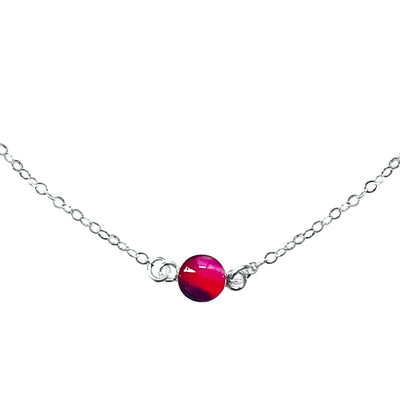 Close up of Circle of hope necklace with 6mm round red, pink and purple pendant with lupus cell image in resin on sterling silver chain necklace gives back