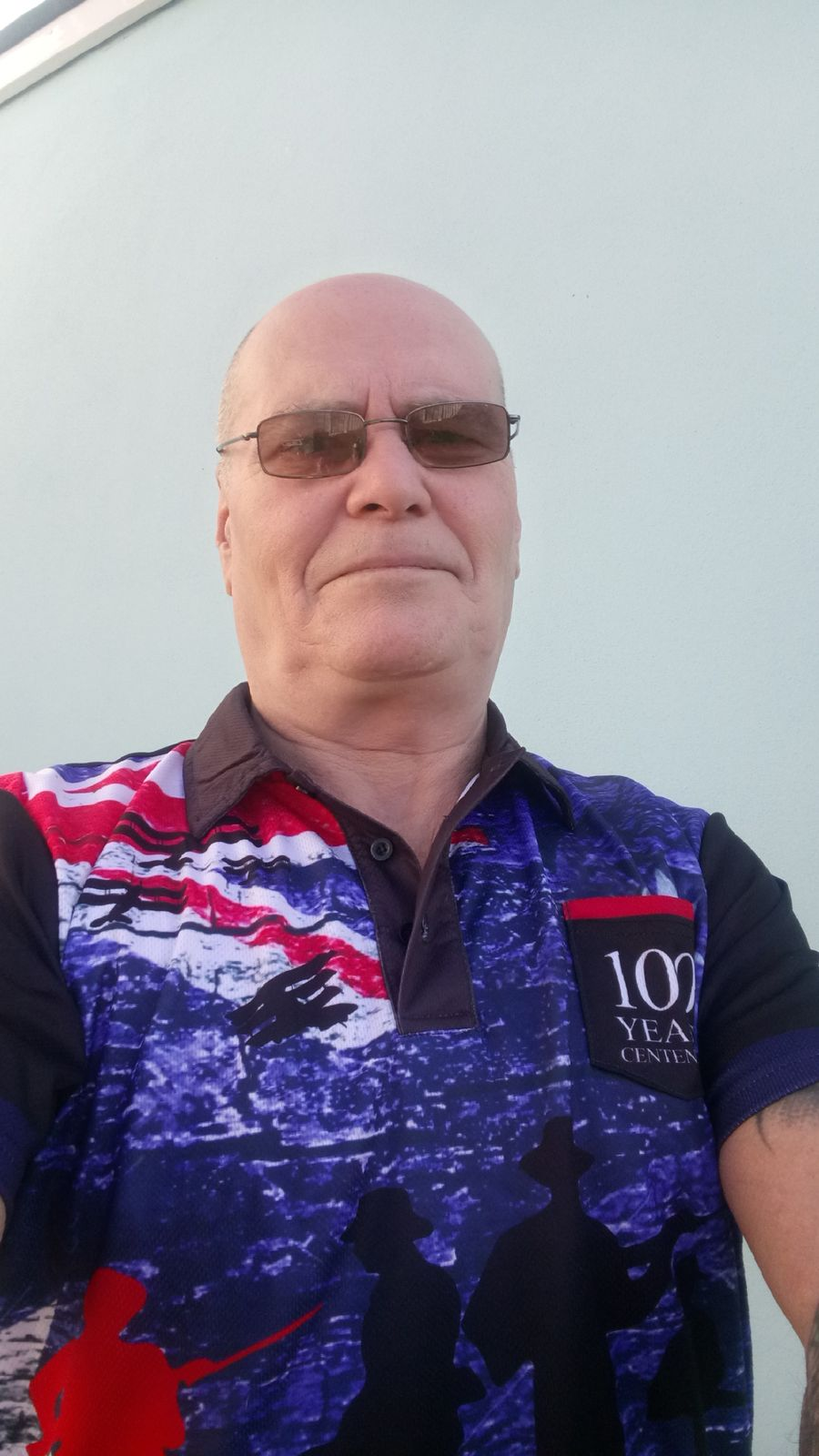 A Person wearing The Spirit Lives On Centenary Blue Polo, Front View 3
