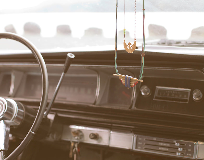 Two necklaces dangle on a rearview mirror.