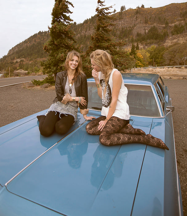 Models hanging out on the top of a vintage car.