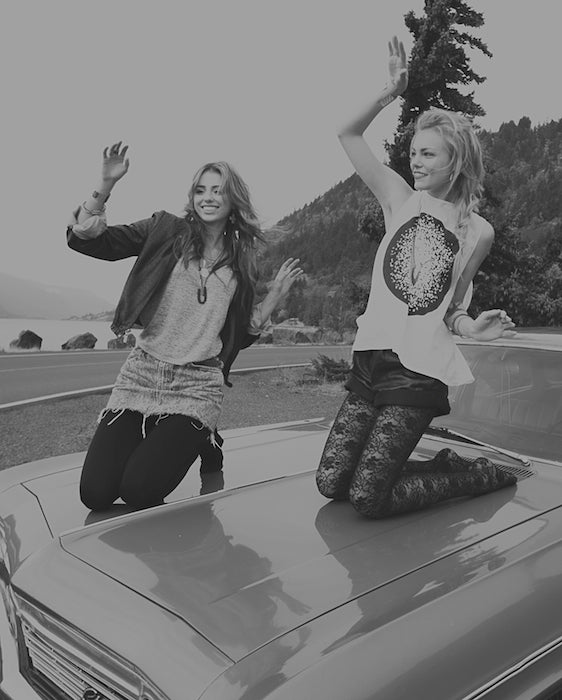 betsy and iya models dancing on top of an antique car.