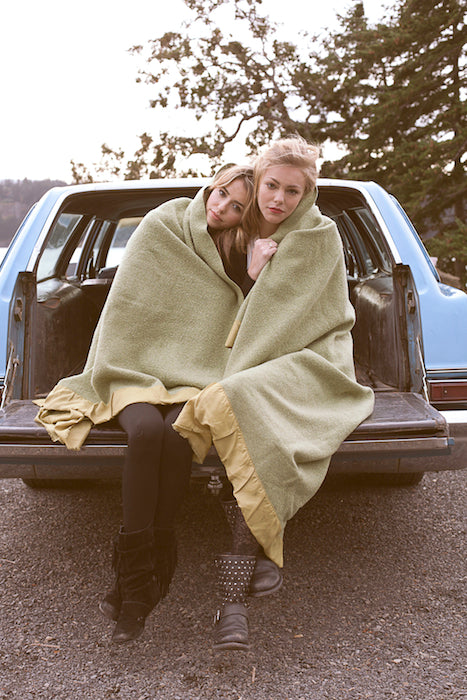 Models sweetly cuddling with a blanket on the back of a vintage car.