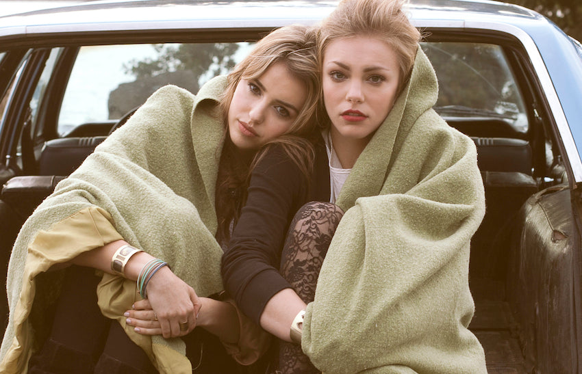 Models warming up in the back of an antique blue car.